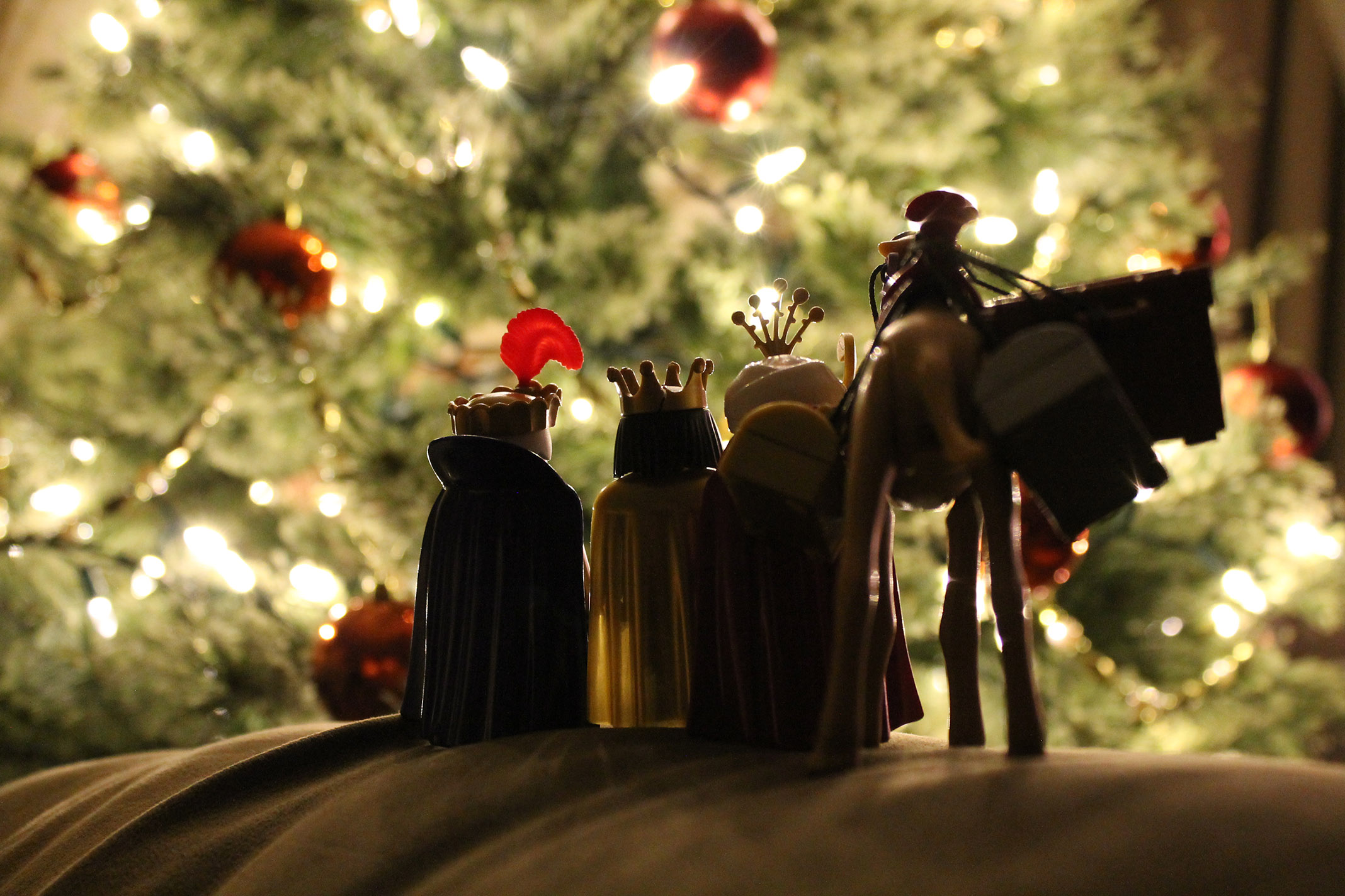 The three wisemen, Balthazar, Melelchior, and Gaspar, gaze upon an illuminated Christmas Tree.