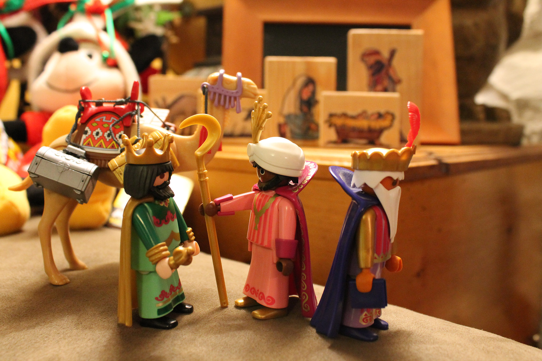Three wisemen and a wooden manger behind them.