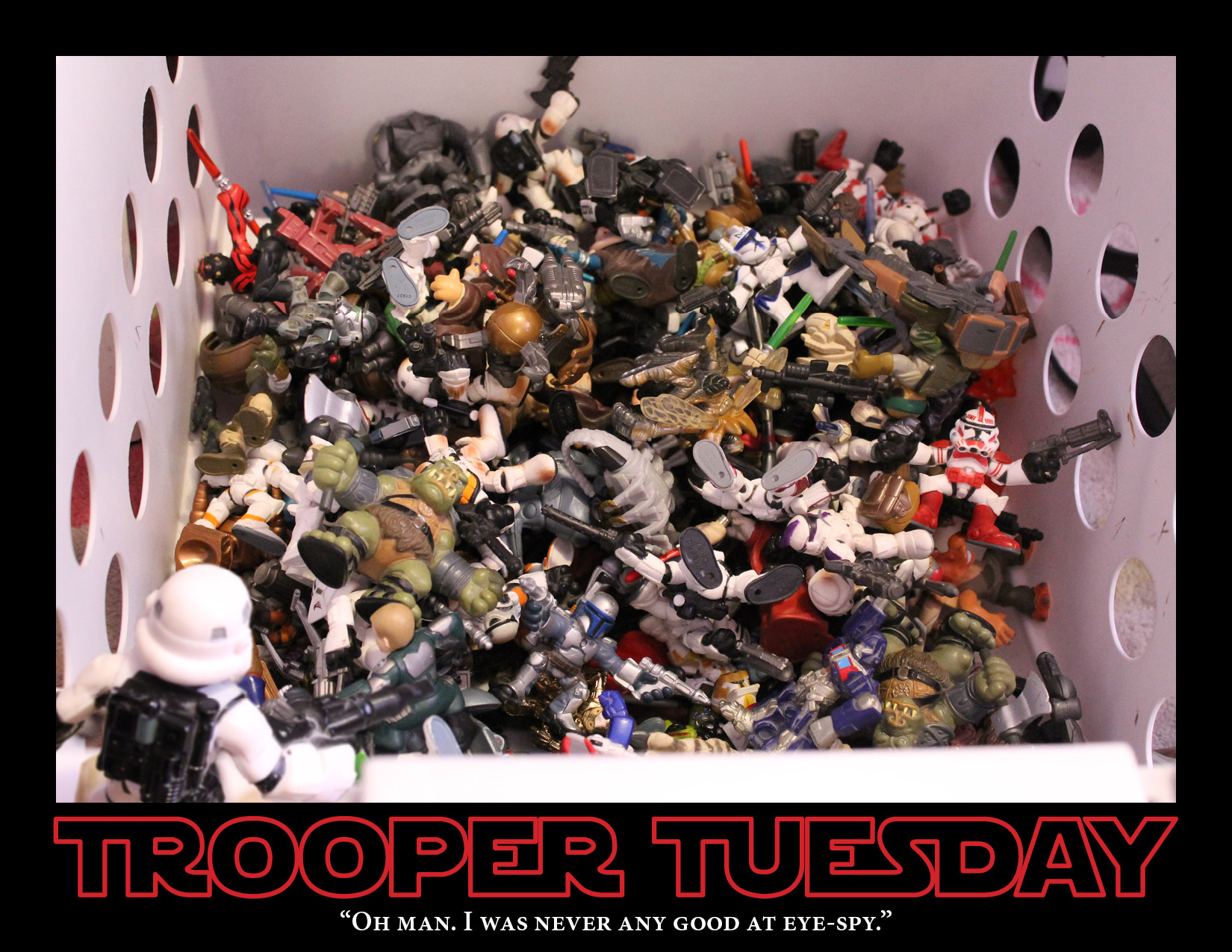 A Stormtrooper stand over a bin full of toys Star Wars figures.