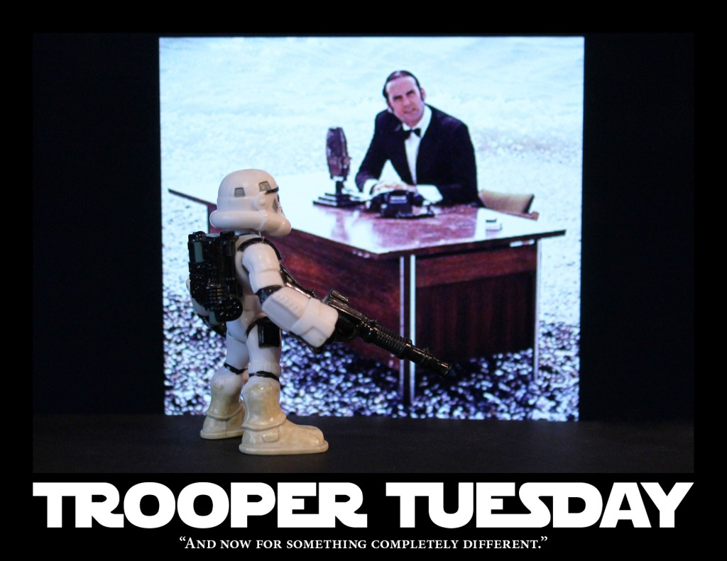 A Sandtrooper stand in front of John Cleese, who is sitting at a desk.