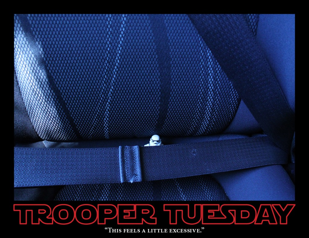 A toy Star Wars Stormtrooper sits in a car seat and is seatbelted in-place.